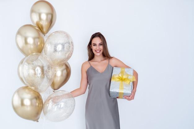 La foto di una ragazza felice tiene in mano una grande confezione regalo avvolta e molti palloncini d'aria sono venuti alla celebrazione della festa