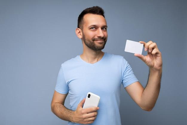 Foto di felice bel giovane brunet con la barba lunga con la barba che indossa una maglietta blu di tutti i giorni isolata