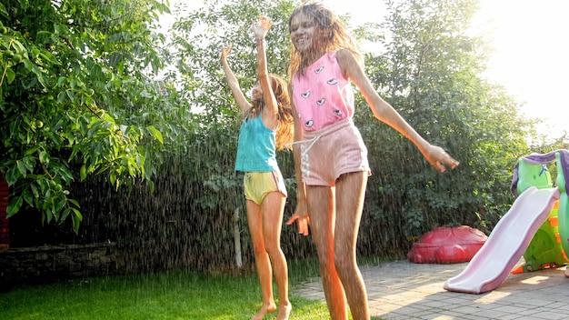 Foto di bambini felici che ridono in vestiti bagnati che saltano e ballano sotto la pioggia calda in giardino. la famiglia gioca e si diverte all'aperto in estate