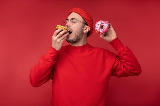 Foto di uomo felice con la barba in occhiali e vestiti rossi. divertiti a mangiare ciambelle dolci, isolate su sfondo rosso.