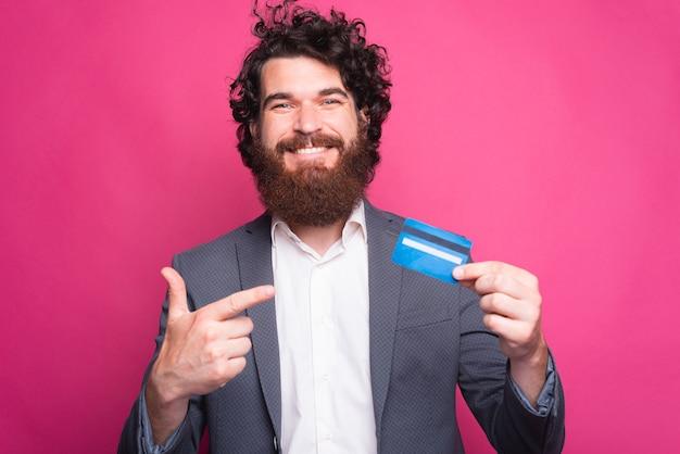 Foto di uomo felice con la barba che indossa la tuta e che punta alla carta di credito blu