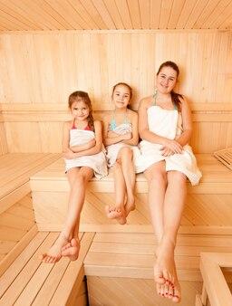 Foto di una madre felice con due figlie che si rilassano al bagno di vapore