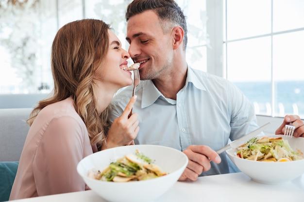 Foto delle coppie romantiche felici cenando e mangiando i salati insieme, mentre riposando nel caffè della città durante la pausa pranzo