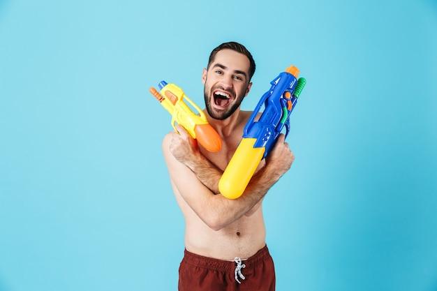 Foto di un turista felice a torso nudo che indossa pantaloncini che ride mentre tiene in mano i giocattoli della pistola ad acqua isolati sopra il blu