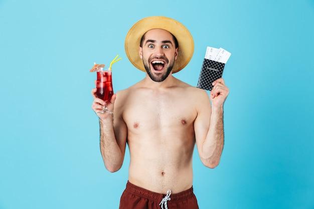 Foto di un turista felice senza camicia che indossa un cappello di paglia che sorride mentre tiene in mano un cocktail e biglietti di viaggio con passaporto isolato