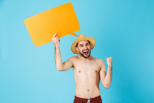 Foto di un turista felice a torso nudo che indossa un cappello di paglia che sorride mentre tiene in mano un cartello giallo copyspace isolato su blu