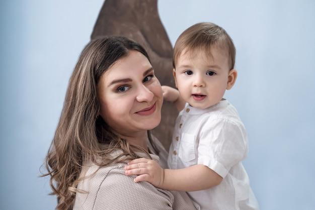 Foto di una madre sorridente felice con un giovane figlio in braccio.