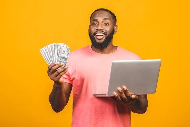 Foto di una posa bella afroamericana felice del giovane isolata sopra il fondo giallo della parete facendo uso dei soldi della tenuta del computer portatile.