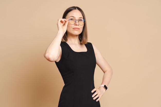 Foto di felice giovane donna d'affari caucasica con gli occhiali in piedi sul muro beige