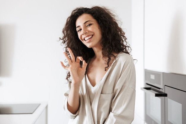 Foto di felice giovane donna riccia con lunghi capelli scuri che indossa abiti di seta per il tempo libero sorridente e mostrando segno ok mentre si trovava in cucina a casa