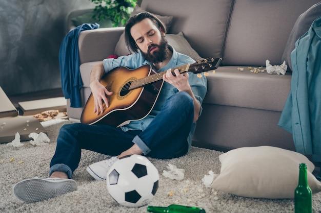 La foto del ragazzo hipster con la barba lunga che si siede sul tappeto vicino al divano che tiene la chitarra non importa il caos dopo la festa di addio al celibato sporco piatto cantando canzoni persona incurante al chiuso