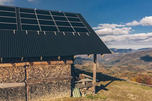 Foto di una casa in montagna, sul tetto di un pannello solare, tramonto