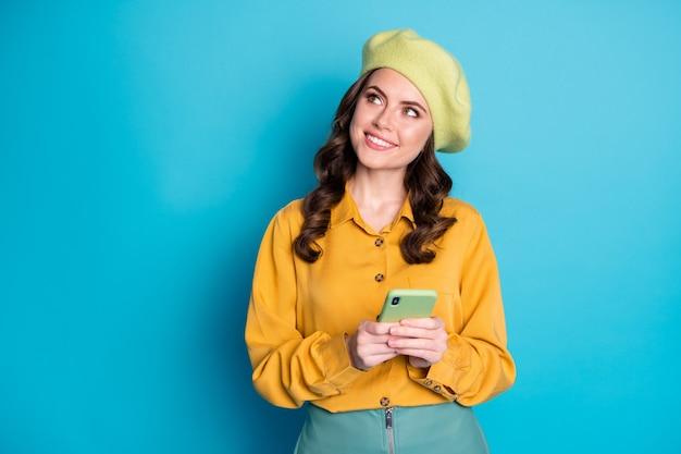 Foto di una ragazza ispirata che usa lo smartphone guarda il piano del copyspace il feedback dei social network chatta agghiacciante indossa un copricapo giallo isolato su uno sfondo di colore blu