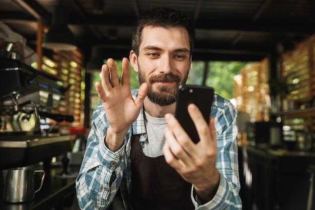 Foto di un gioioso barista che indossa un grembiule che sorride mentre usa lo smartphone al bar o al caffè all'aperto