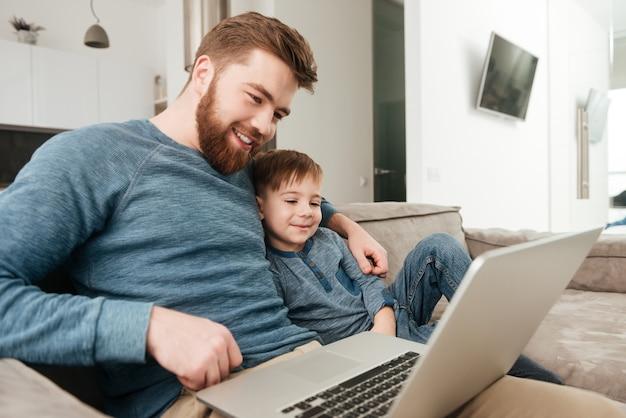 Foto del padre gioioso che utilizza il computer portatile con il suo piccolo figlio carino.