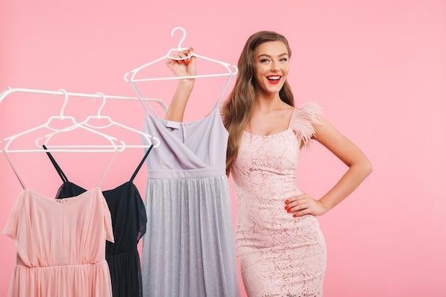Foto di gioiosa giovane donna 20s sorridente e in posa vicino a cremagliera con un sacco di vestiti sui ganci, isolato sopra il muro rosa