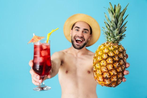 Foto di un gioioso turista a torso nudo che indossa un cappello di paglia che sorride mentre tiene in mano ananas e cocktail isolati