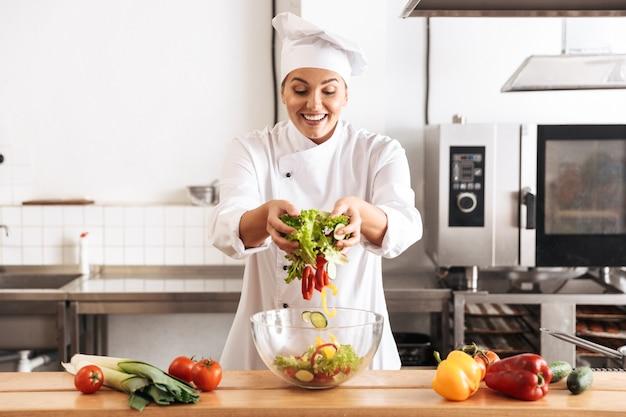 Foto di gioiosa donna chef indossando l'uniforme bianca che produce insalata con verdure fresche, in cucina al ristorante