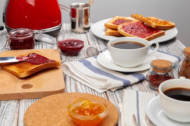 Foto del tavolo da cucina con toast, marmellate di frutta e coltello