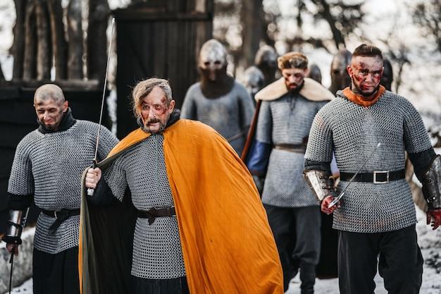 Foto dei cavalieri in armatura con le spade durante la guerra. emozioni malvagie di un guerriero che va a combattere con la spada