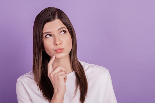 Foto di una signora che cerca lo spazio vuoto labbra carnose braccio pensante sul mento isolato su sfondo viola