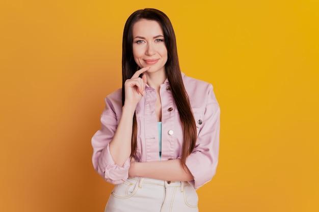 Foto di una donna che pensa con il braccio sul mento isolato su sfondo giallo