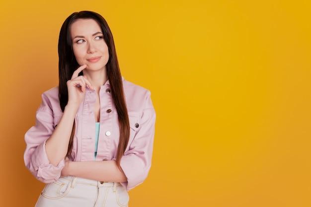 La foto del braccio pensante della signora sul mento sembra uno spazio vuoto isolato su sfondo giallo