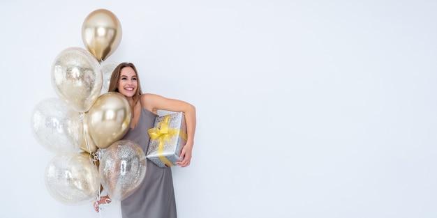 La foto di una ragazza che ride tiene una grande confezione regalo avvolta e molti palloncini d'aria sono venuti alla celebrazione della festa