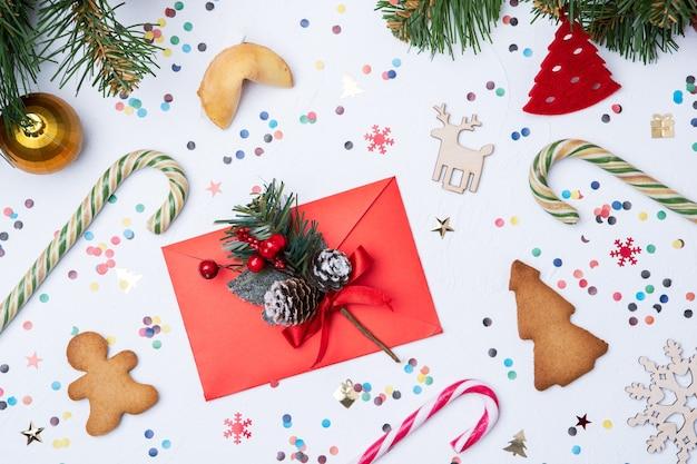 Foto di lettera, abete di natale, caramelle, biscotti sul tavolo bianco