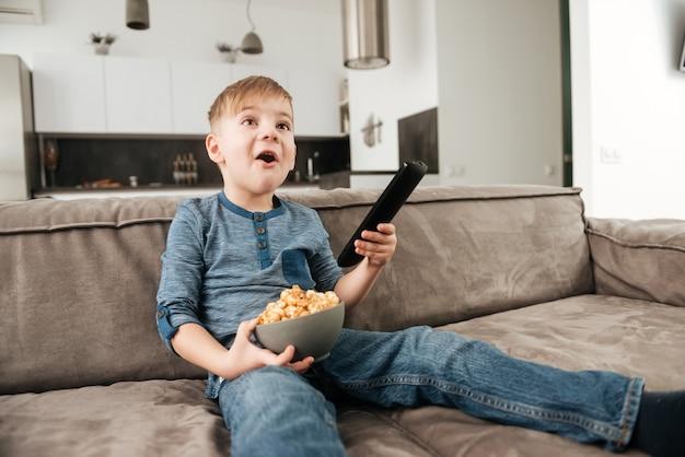 Foto di un ragazzino seduto sul divano con in mano il telecomando mentre guarda la tv e tiene in mano i popcorn.