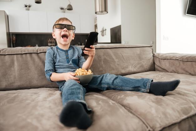 Foto di un ragazzino seduto sul divano con in mano il telecomando mentre guarda la tv con occhiali 3d che tengono in mano i popcorn.