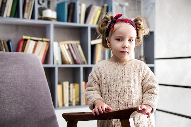 Foto di bambina vicino a uno scaffale con libri che esamina la macchina fotografica