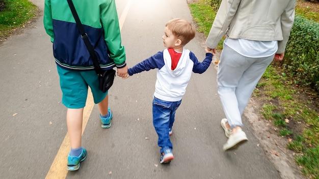 Foto di un bambino piccolo che tiene per mano sua madre e suo fratello maggiore e cammina nel parco autunnale