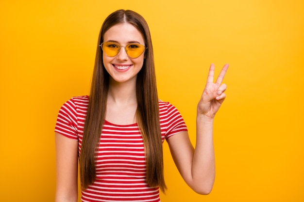 Foto di bella ragazza abbastanza disattenta con la pettinatura lunga sorridente spettacolo v-sign accogliente persone festa studentesca indossare occhiali da sole a righe camicia rossa bianca vibrante sfondo di colore giallo
