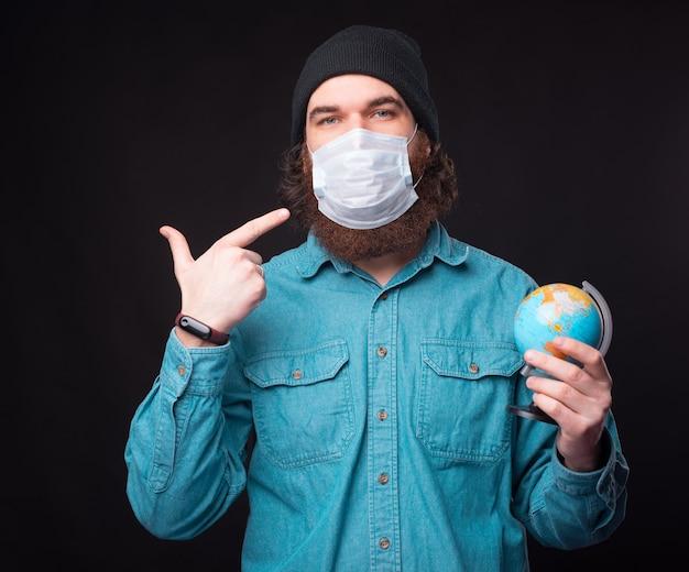 Foto dell'uomo che indica la sua maschera medicinale e che tiene il globo