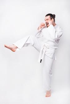 Foto di un uomo che pratica il taekwondo e fa un calcio con una gamba