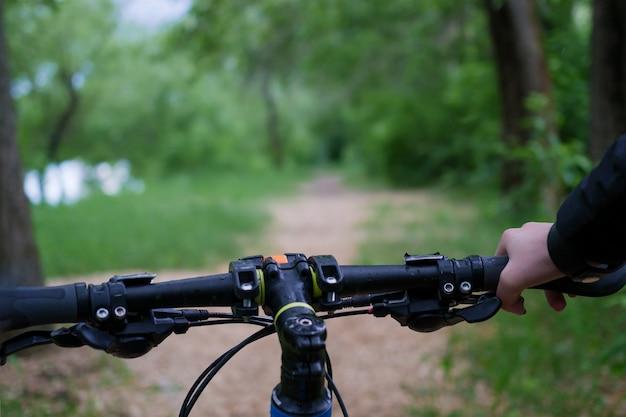 Foto della mano dell'uomo e del timone della bicicletta