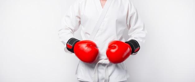 Foto di uomo che indossa dobok uniforme taekwondo con guantoni da boxe rossi