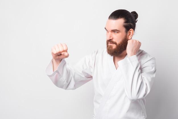 Foto dell'uomo con la barba che indossa la formazione uniforme di taekwondo sopra il muro bianco