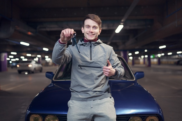 Foto di un uomo con le chiavi in piedi in macchina nel parcheggio sotterraneo