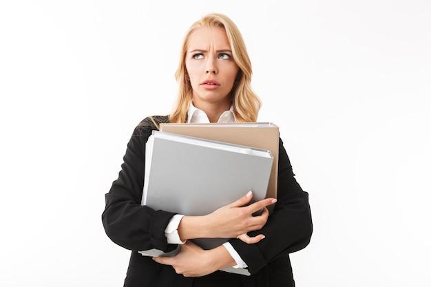 Foto della ragazza del responsabile che indossa la tuta da ufficio che tiene le cartelle di carta nelle mani, isolata