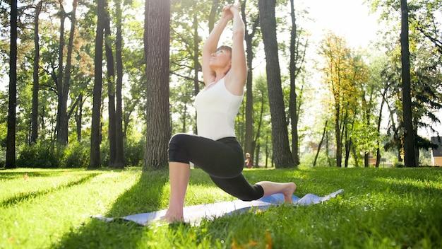 Foto di donna di mezza età che pratica yoga o fitness su erba verde fresca al parco. salute fisica e mentale femminile. persona in meditazione e armonia di corpo e anima