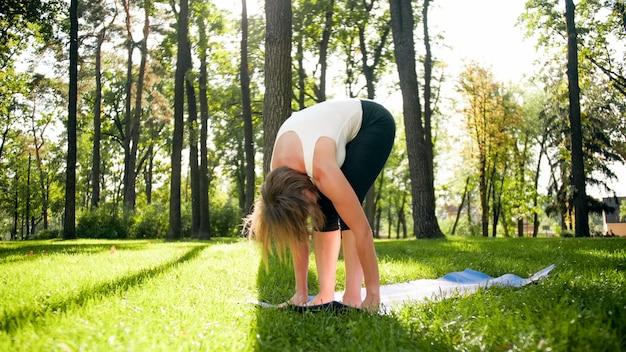 Foto di donna di mezza età in abiti sportivi che praticano yoga all'aperto al parco. donna di mezza età che si allunga e medita nella foresta