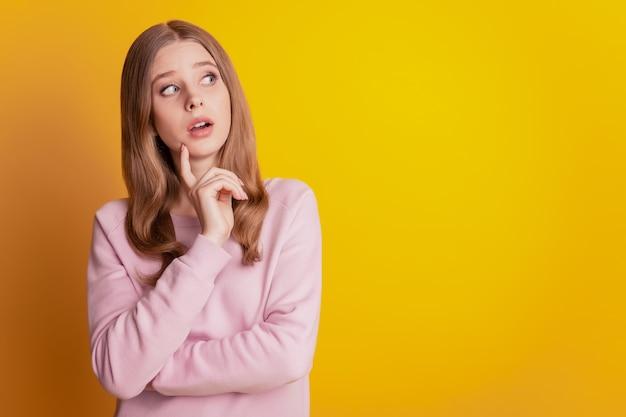 La foto del mento del dito della ragazza intelligente e intelligente cerca lo spazio vuoto su sfondo giallo