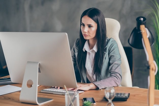 Foto di una ragazza pensierosa agente di marketing capo sedersi al tavolo lavoro computer remoto sfogliare le informazioni sulla crescita delle crisi di avvio indossare giacca formale giacca sportiva nella postazione di lavoro
