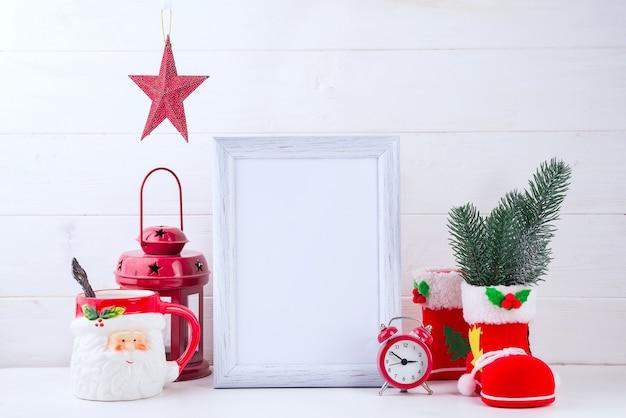Foto mock up con cornice bianca, stella di natale in un vaso di fiori e lanterna rossa su legno bianco