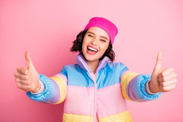 Foto di bella signora che consiglia la novità fresca in aumento i pollici in su indossare un cappotto colorato caldo isolato su sfondo rosa