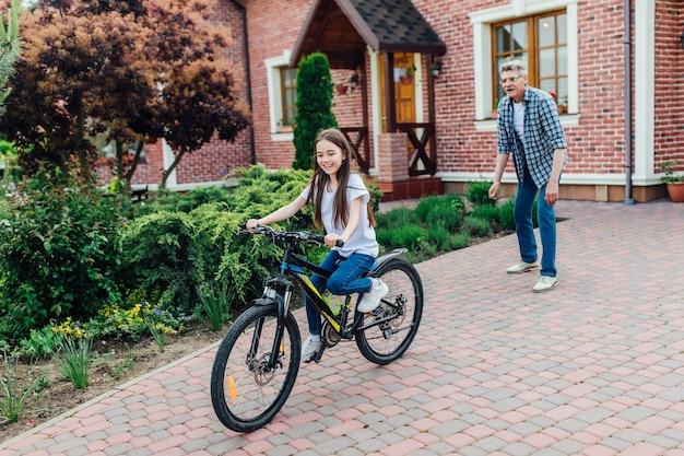 La foto del nonno più anziano e barbuto sta imparando alla figlia ad andare in bicicletta nel cortile di casa.