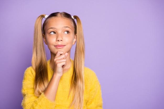 Foto della ragazza casuale pensierosa che tocca il suo mento che porta maglione giallo che esamina lo spazio vuoto isolato sopra la parete di colore viola pastello