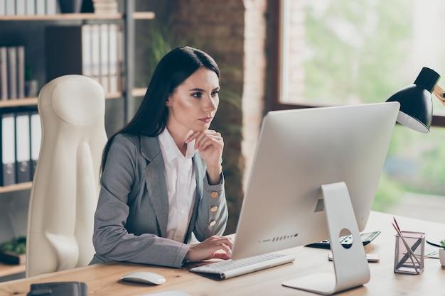 Foto di una ragazza dal colletto pensieroso si siede al tavolo lavora a distanza guarda lo schermo del computer del computer analizza il lavoro dell'azienda il progetto del mercato indossa la giacca blazer sul posto di lavoro ufficio moderno